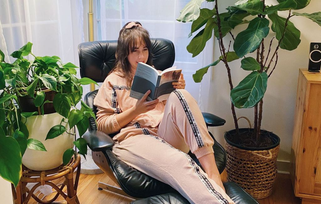 1SE team member Emily reads a novel in a lounge chair, flanked by houseplants.