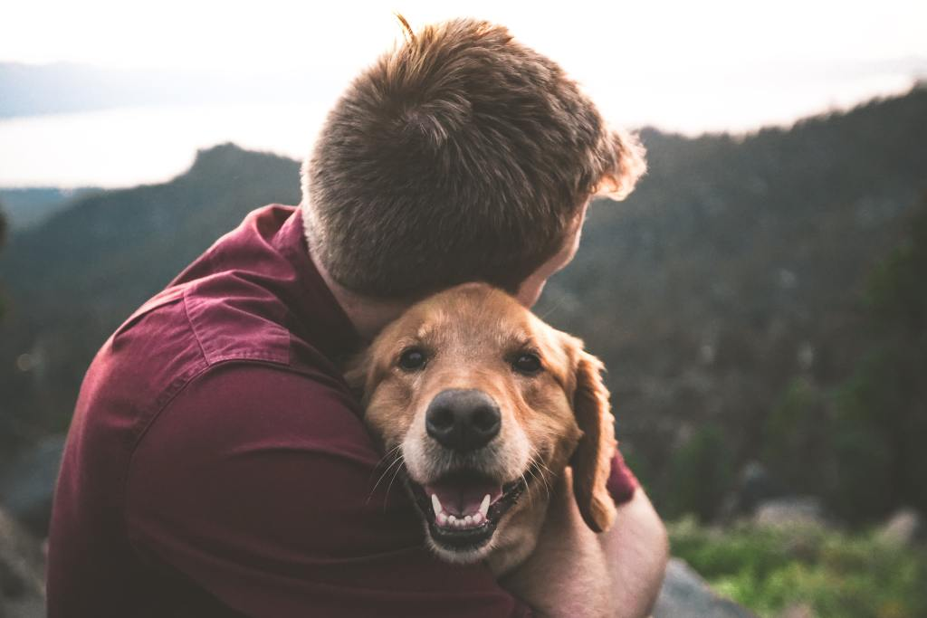 a man hugs a smiling dog
