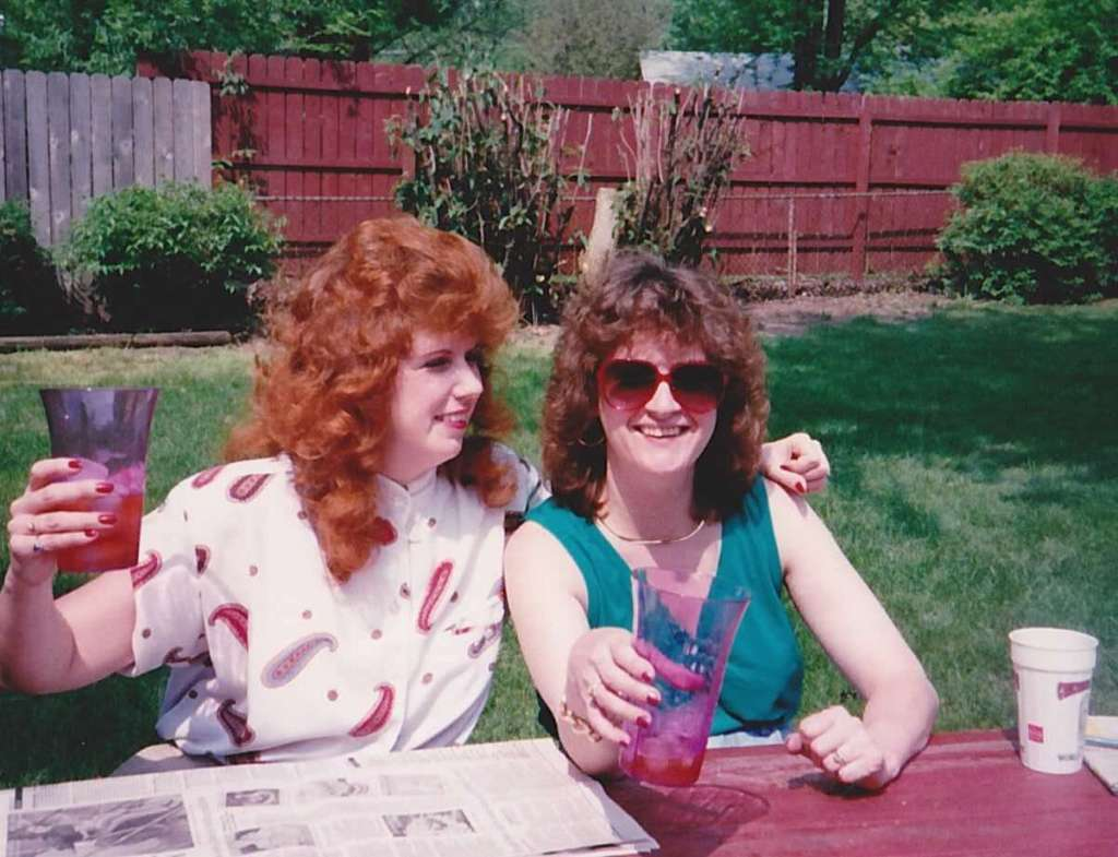 the author's mother and aunt sit smiling at a picnic bench in the sun.